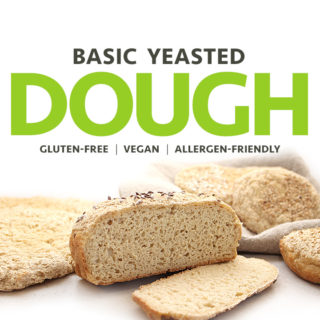 A picture of a yeasted, gluten-free, and vegan sliced loaf of bread, with a pizza crust and buns in the background. Free of all top allergens. freshisreal.com