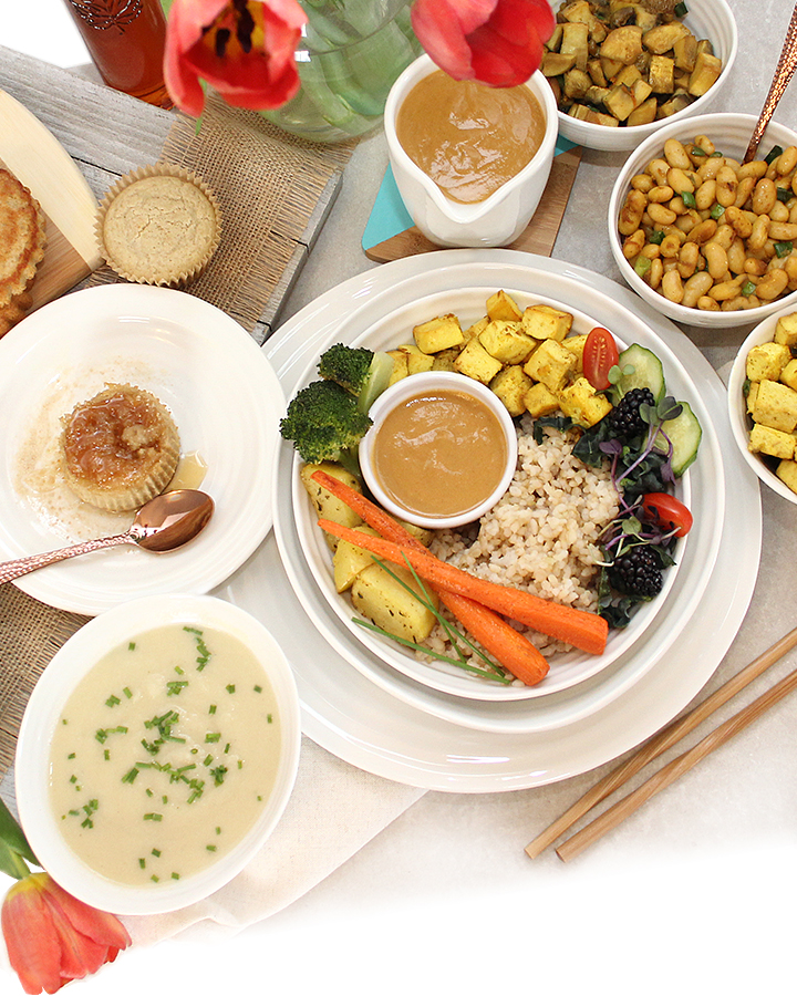 A beautiful, colourful assortment of plant-based dishes like soup, a mini maple sourdough cake, vegan gravy, and yellow turmeric tofu served in a bowl brown rice and roasted veggies. Perfect for brunch. Free of all top allergens. freshisreal.com