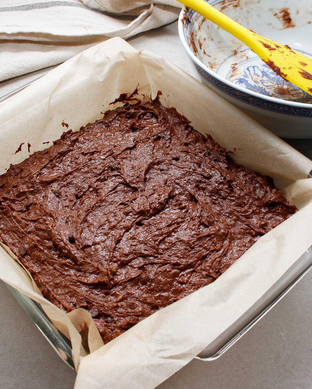 Gluten-free vegan brownie batter in square baking pan.