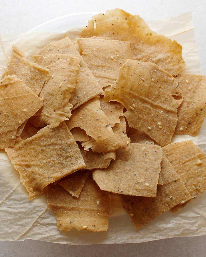 GF sourdough chips on parchment paper.