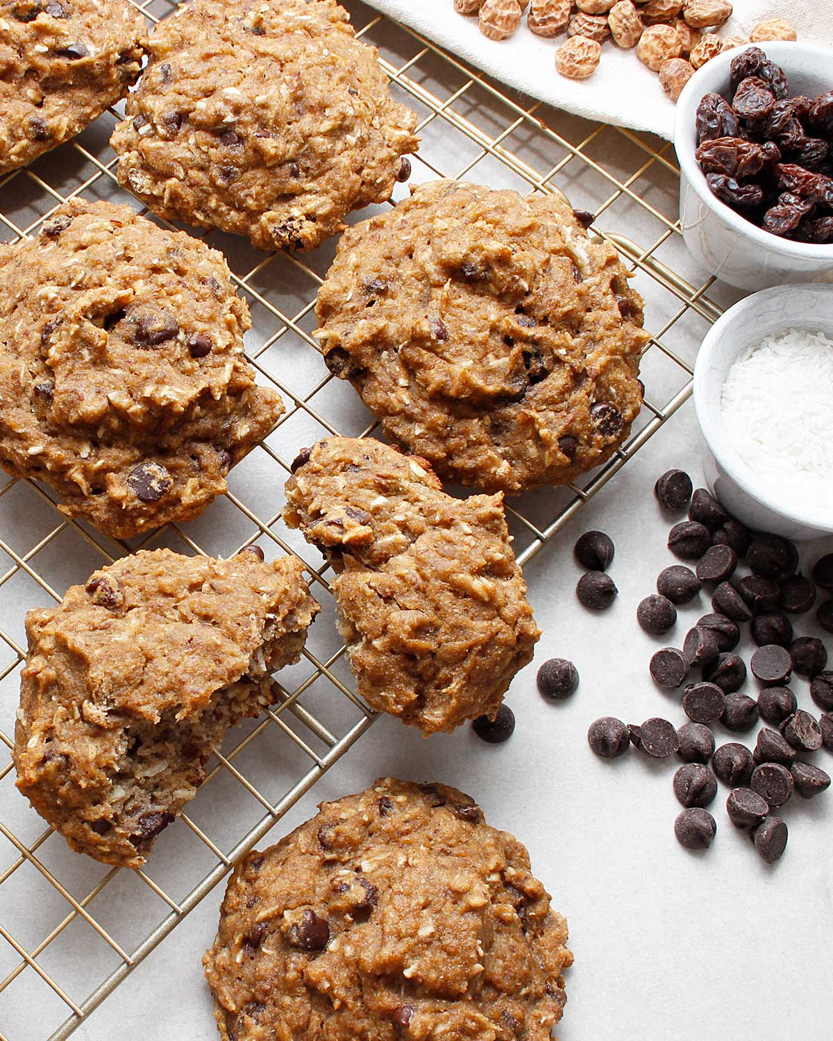Grain-free banana bread cookies with allergen-friendly chocolate chips cooling on wire rack.