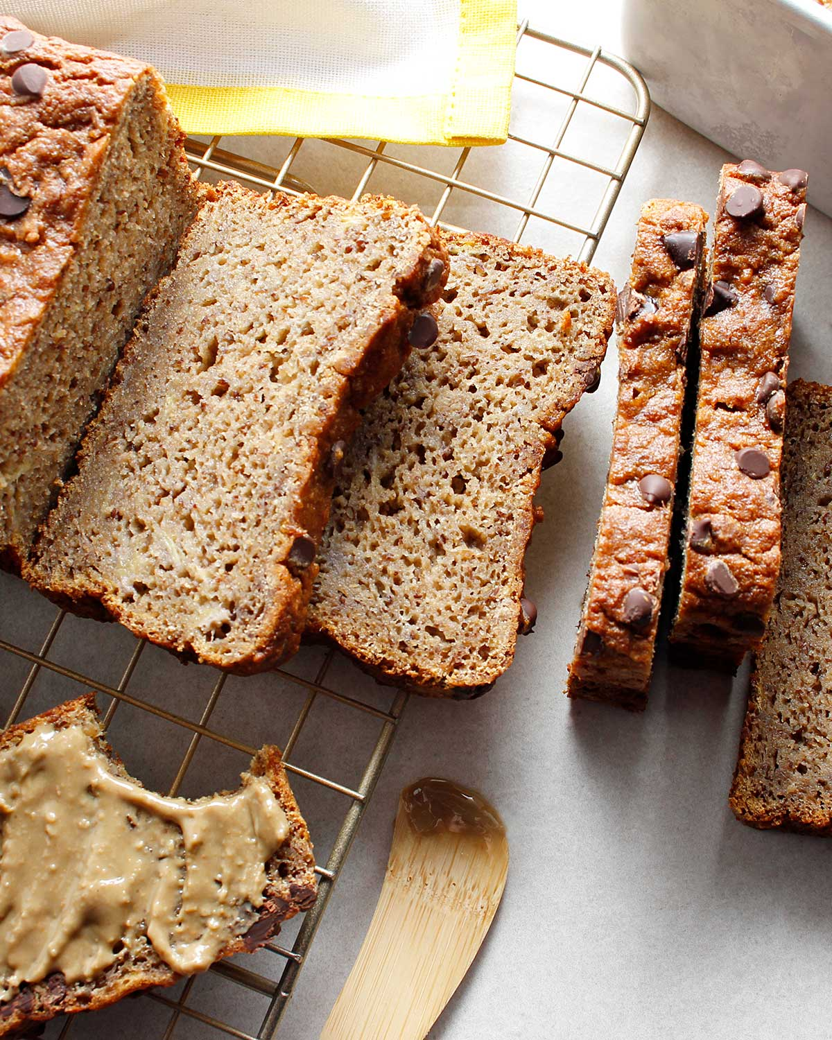 Close up of sliced grain-free banana bread with chocolate chips decorating the top. A slice is off to the left side, spread with seed butter.