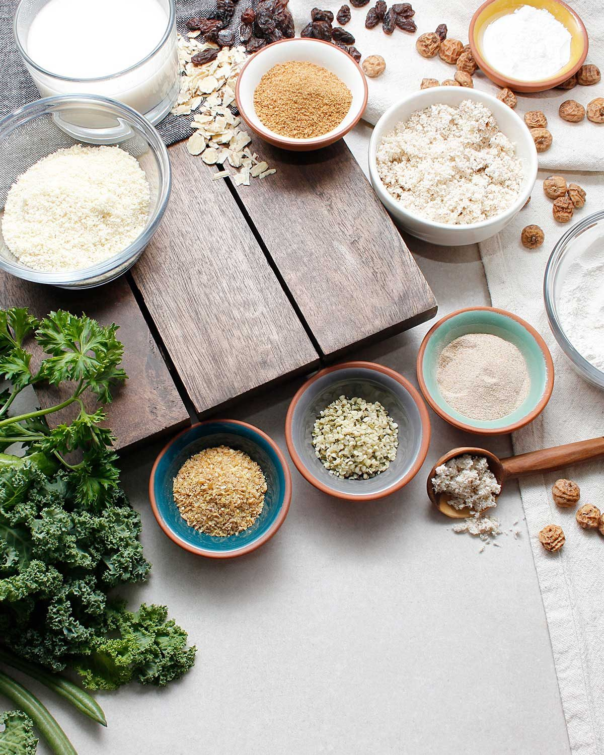 Grain-free ingredients in small bowls including some fresh greens.