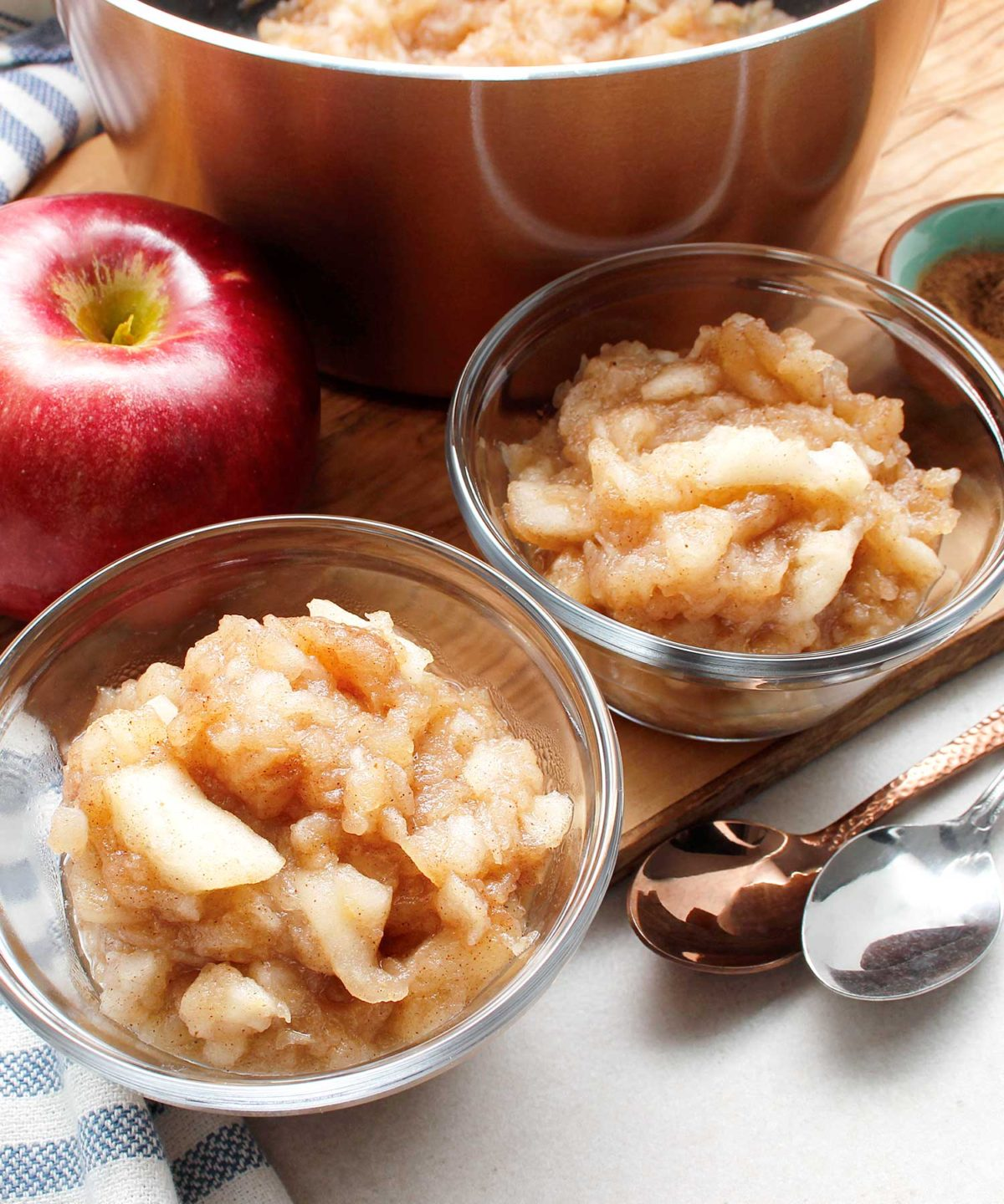 Two small glass bowls of homemade chunky style applesauce.