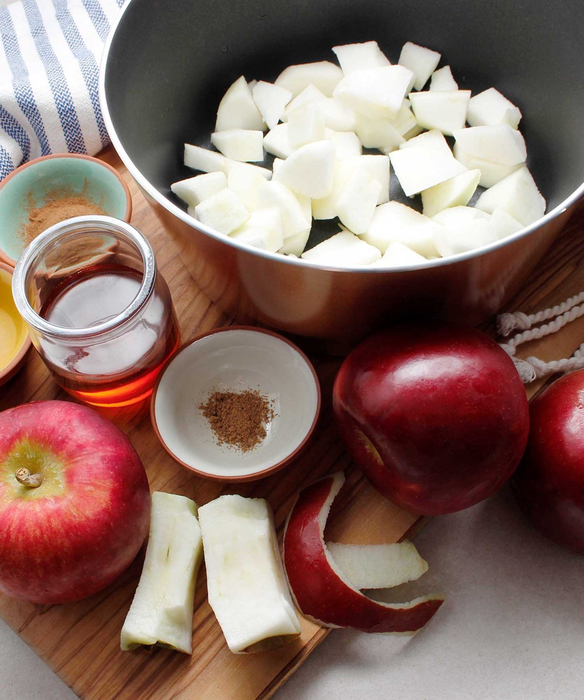 Ingredients to make chunky homemade applesauce: cortland apples, maple syrup, cinnamon, nutmeg and fresh lemon juice.