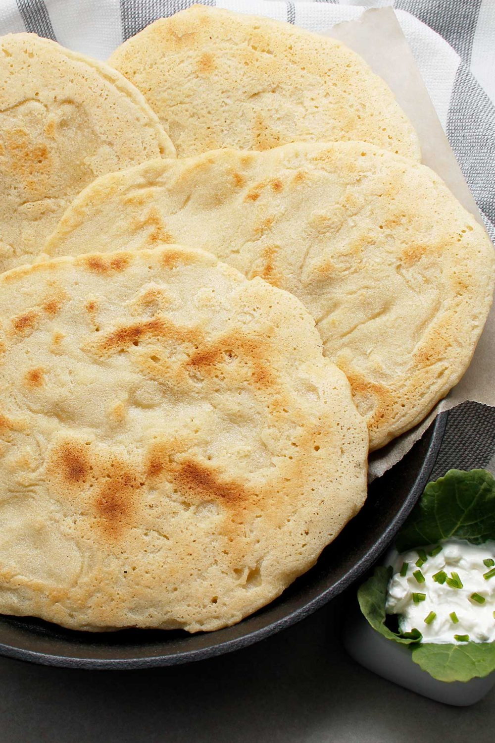 A few freshly baked GF naan breads in a cast iron skillet with dip on the side.