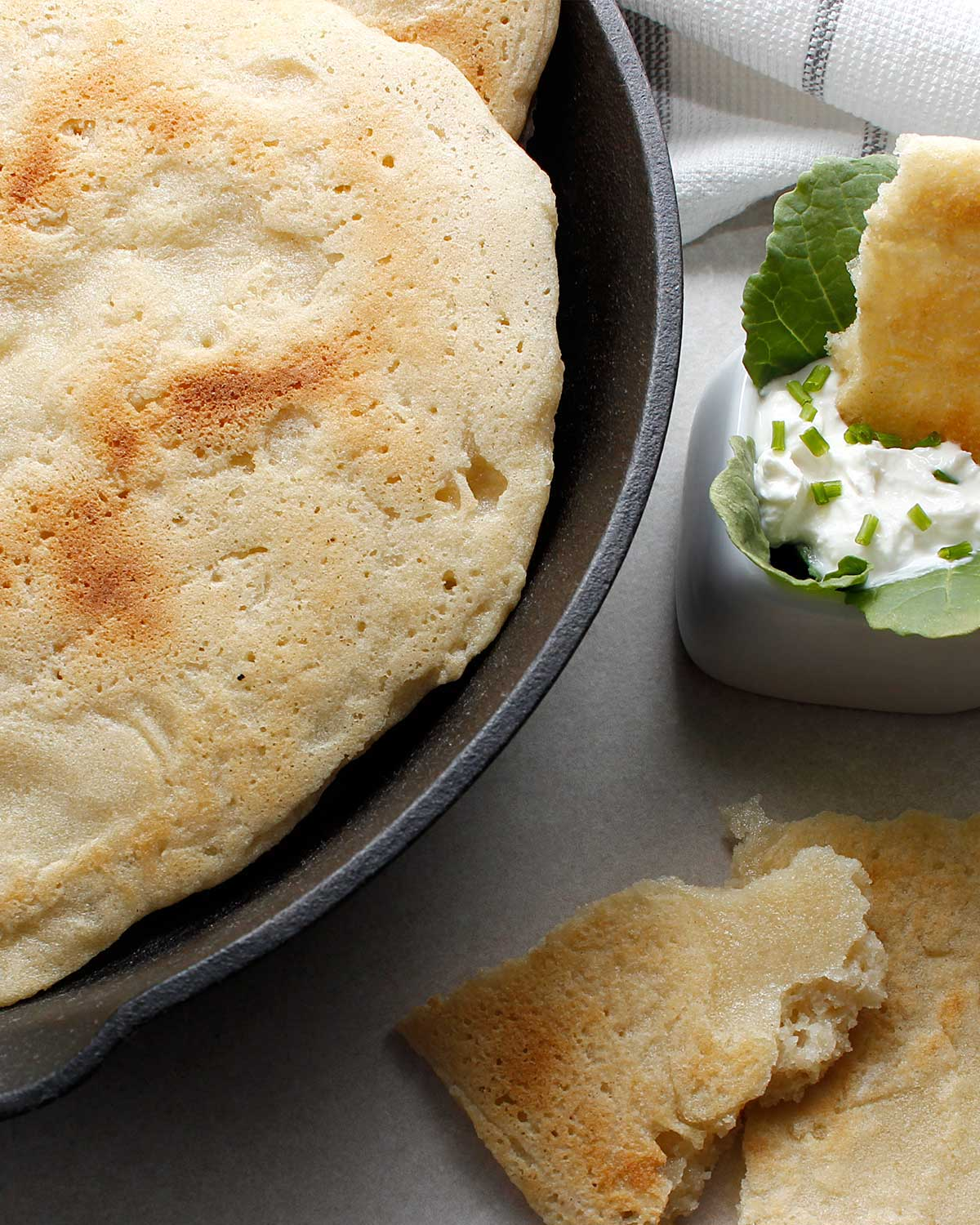 Gluten-free sourdough naan bread in a skillet with pieces on the side with one dipped in a white garlic dip.