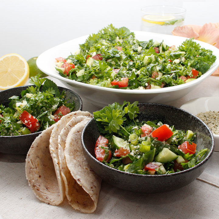 Tabbouleh salad in one large bowl and 2 smaller bowls in the front with cassava flatbread