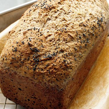 A freshly baked gluten-free vegan loaf of bread cooling on a wire rack.
