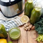 Green juice in glass and bottles with juicer in background.